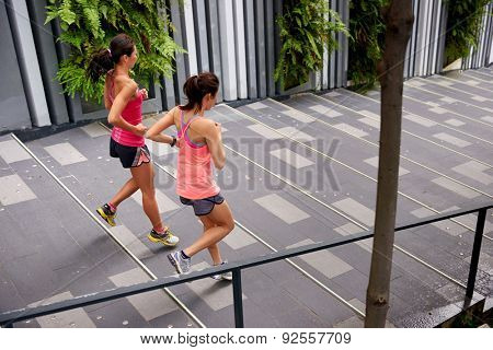 sporty women running down stairs outdoors for morning workout