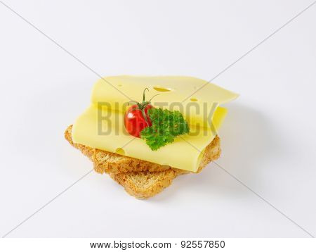 toast bread with two slices of cheese and whole cherry tomato