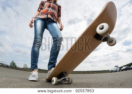 Rider standing on the asphalt road with the skateboard