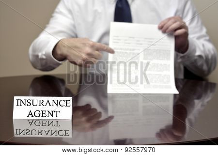 Insurance agent sitting at desk holding blank contract