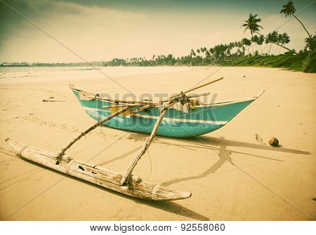 Untouched tropical beach with fishing boat in Sri Lanka - retro style photo