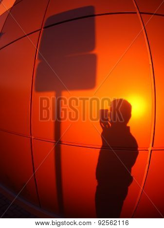 The Silhouette Of A Man On A Red-orange Wall, Who Photographs A Road Sign