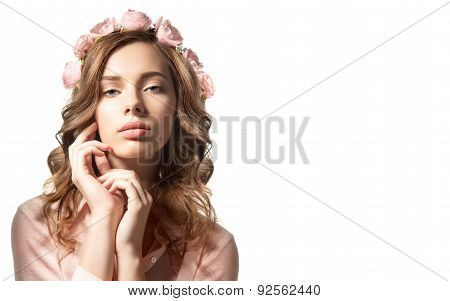Girl in a wreath of flowers roses with curly hair