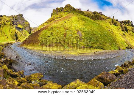The canyon Pakgil is located among fantastic rocks. On a bottom of a canyon  fast shallow stream flows. The summer blossoming Iceland. The photo was taken Fisheye lens