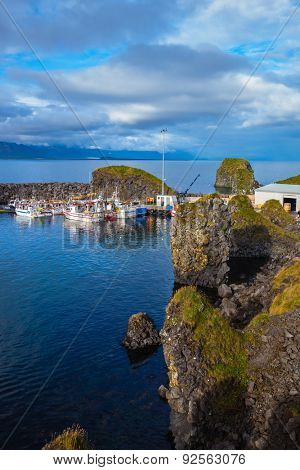 White fishing boat in the harbor pier fishing village Arnastapi. Sunset on the sea fjord in Iceland