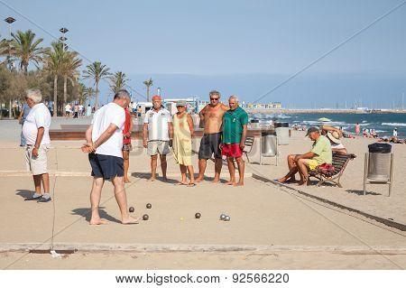 Seniors Spaniards Play Bocce On A Sandy Beach