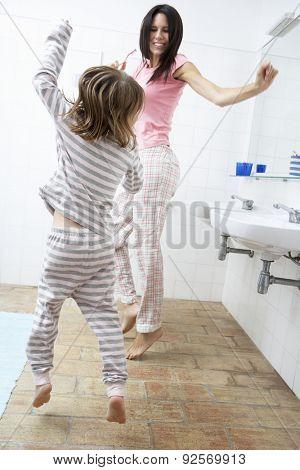 Mother And Daughter Having Fun In Bathroom Brushing Teeth