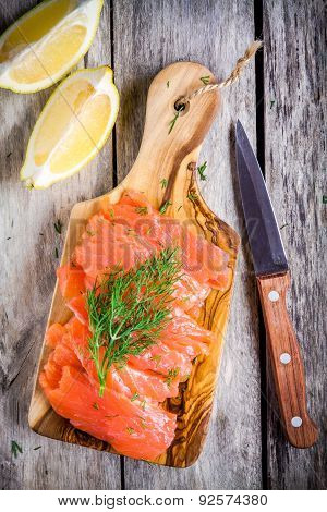 Slices Of Smoked Salmon On A Wooden Chopping Board With Dill