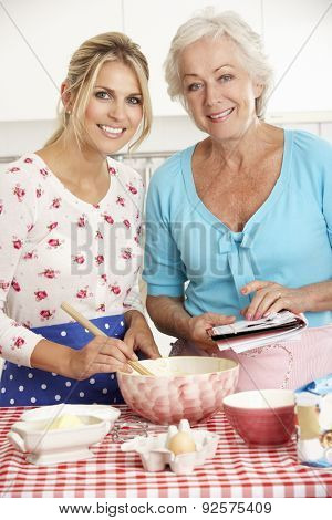 Senior Woman And Adult Daughter Baking In Kitchen