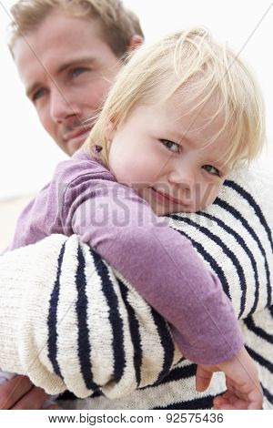 Father Cuddling Young Daughter Outdoors