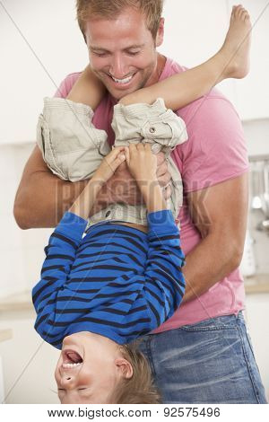 Father Holding Son Upside Down At Home