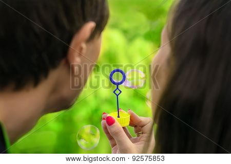 Young Couple Having Fun With Soap Bubbles In The Park