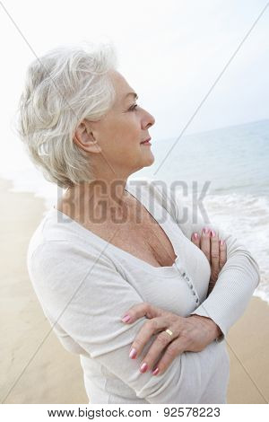 Thoughtful Senior Woman Standing On Beach