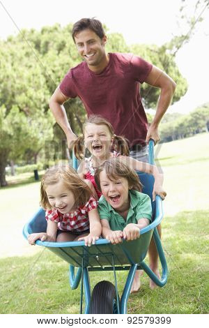 Father Giving Children Ride In Wheelbarrow