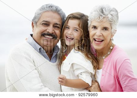 Portrait Of Grandparents On Beach With Granddaughter