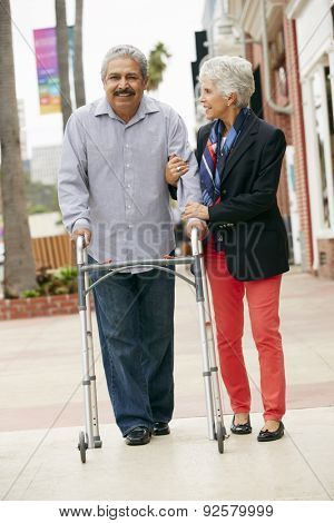 Wife Helping Senior Husband To Use Walking Frame