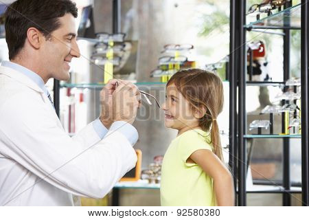 Optician Helping Girl To Choose Glasses