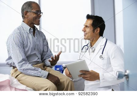 Doctor In Surgery With Male Patient Using Digital Tablet