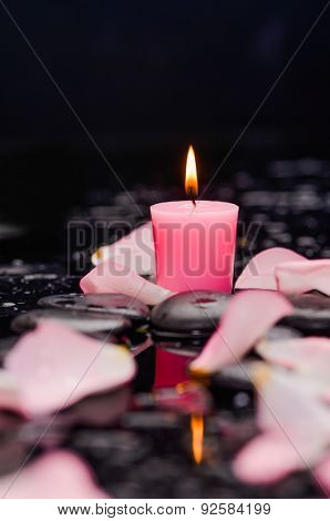Reflection of pink rose petals with pink candle and therapy stones