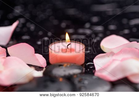 pink rose petals with pink candle and therapy stones