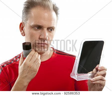 confused man before a mirror the first time tries a man's against wrinkles cream