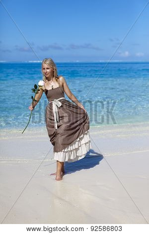The beautiful woman with a rose on the edge of the sea on a beach. Polynesia.