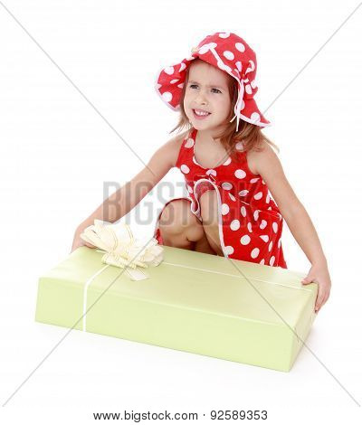 Beautiful girl in a red dress and hat polka dot bent down to exa