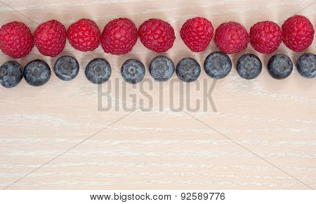 Line Of Rasberry And Bilberry On The Wooden Background