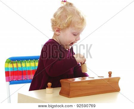 Adorable Caucasian little girl playing with Montessori material