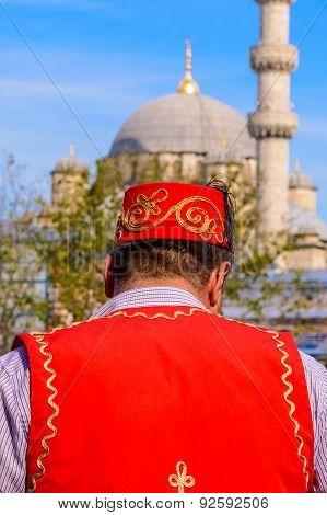 ISTANBUL, TURKEY - MAY 2015 - A man in traditional clothes in front of the New Mosque in Istanbul