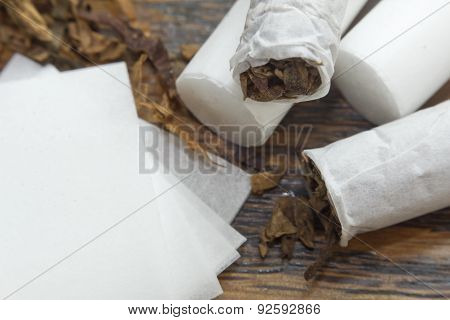 Rolling cigarettes with filters papers and plenty finely cut tobacco