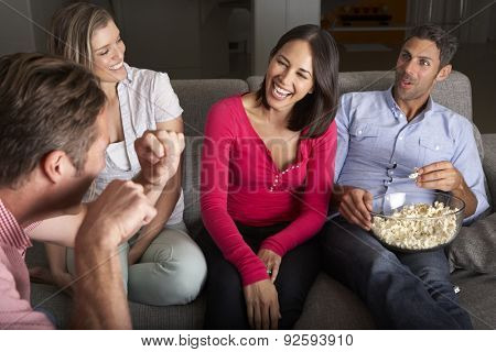 Group Of Friends Sitting On Sofa Talking And Eating Popcorn