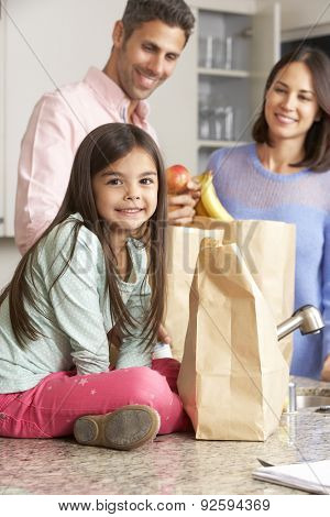 Family Unpacking Grocery Shopping In Kitchen