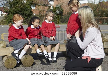 Teacher Comforting Victim Of Bullying In Playground