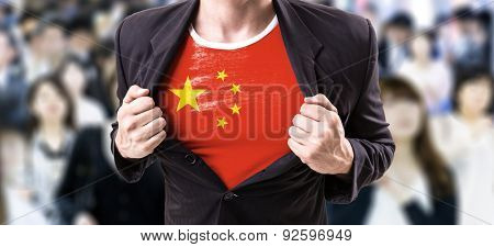 Businessman stretching suit with Chinese Flag with a crowd people on background
