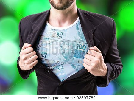 Businessman stretching suit with Brazilian money on bokeh background