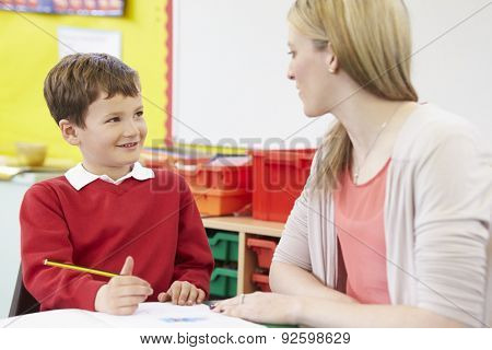 Teacher Helping Male Pupil With Practising Writing At Desk