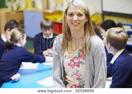 Portrait Of Teacher In Classroom With Pupils