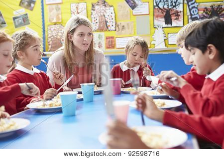 Schoolchildren With Teacher Sitting At Table Eating Lunch