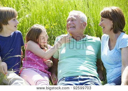 Grandparents With Grandchildren Relaxing In Field Together