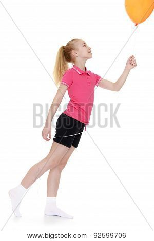 Charming little girl in the red sweater and shorts holding a bal