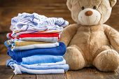 stock photo of baby bear  - Baby clothes stack and teddy bear on a wooden table - JPG