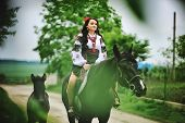 stock photo of horse girl  - Young brunette girl on national dress with horses - JPG