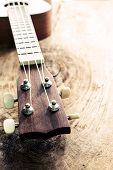 foto of ukulele  - Close up of ukulele on old wood textured with hard light Vintage tone - JPG