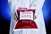 pic of hemostasis  - closeup of a doctor showing a blood bag with a sticker with the text give life - JPG