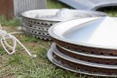 pic of yard sale  - Stacks of vintage chrome hubcaps on the grass at a yard sale - JPG