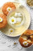 image of chamomile  - Glass of chamomile tea with chamomile flowers and tasty muffins on color wooden background - JPG
