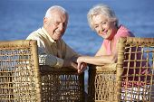 stock photo of couple sitting beach  - Senior Couple Sitting In Chairs Relaxing On Beach - JPG
