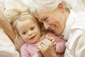 picture of cuddle  - Grandmother Cuddling Granddaughter In Bed - JPG