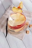 stock photo of cider apples  - Glass of apple cider with fruits and vanilla stick on table close up - JPG